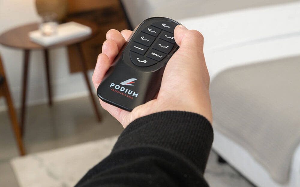 Person holding remote control for Podium adjustable bed